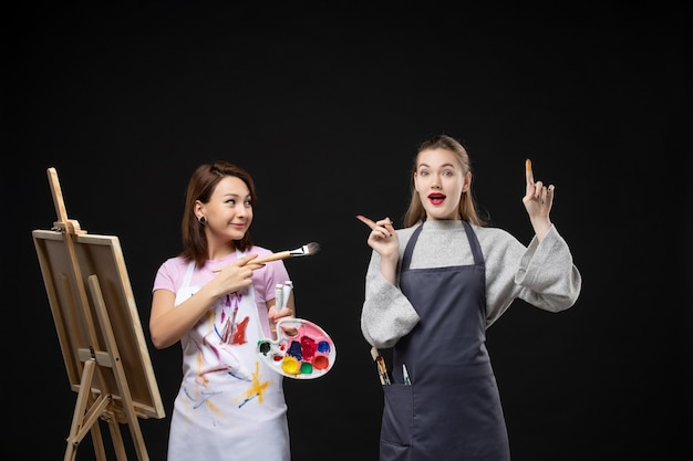Vista frontale pittrice disegno su cavalletto con altra donna su muro nero foto colore arte immagine artista pittura