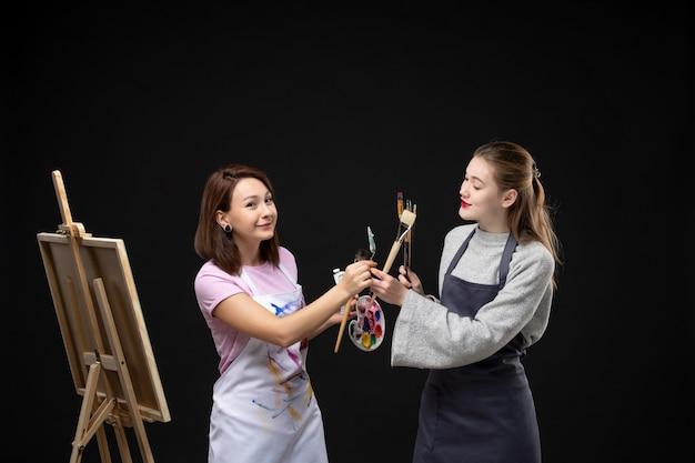 正面図女性画家がイーゼルで他の女性と一緒に黒い机のアーティストの写真カラーアート絵の絵の具の絵を描く