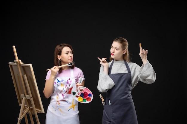 黒い壁に他の女性とイーゼルを描く正面図の女性画家写真カラーアート写真アーティストペイントの仕事