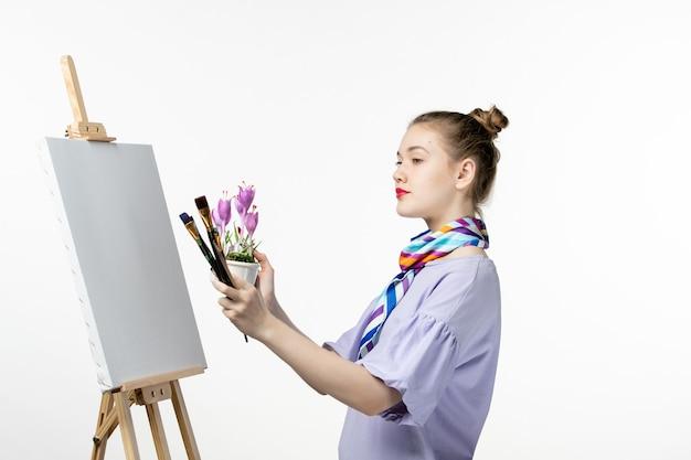 Vista frontale pittrice disegno immagine di fiore su un muro bianco disegnare artista cavalletto matita arte pittura donna