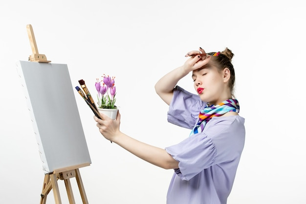 Front view female painter drawing picture of flower on white wall photo artist easel art draw paint