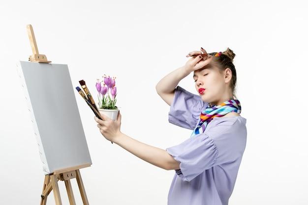 전면보기 여성 화가 흰 벽에 꽃 그림 그리기 사진 아티스트 이젤 아트 그리기 페인트