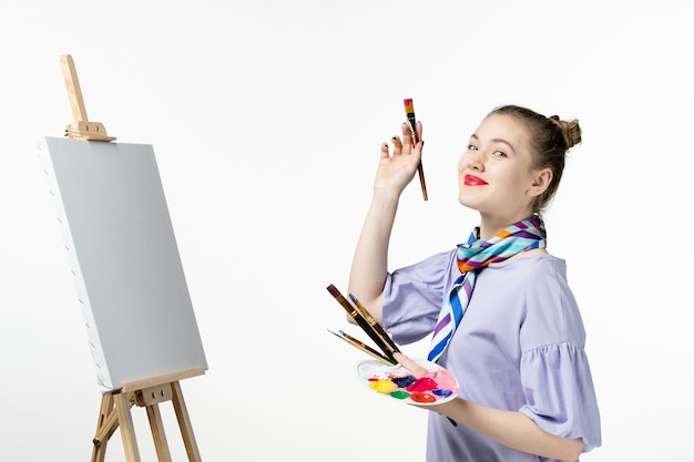 Front view female painter drawing picture on white wall draw artist easel pencil art paint woman
