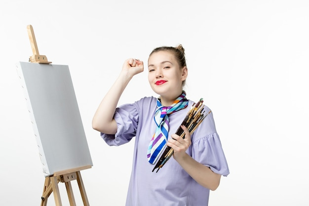 Front view female painter holding tassels for drawing on the white wall woman picture art photo paint draw artist pencil easel