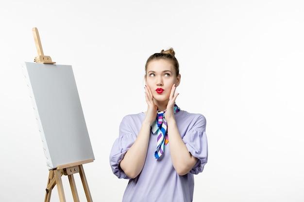 Pittore femminile vista frontale che si prepara a disegnare sul cavalletto sulla mostra d'arte della parete bianca artista di pittura nappa