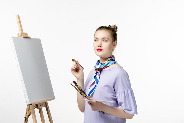 Vista frontale pittrice che si prepara a disegnare su una foto di arte della parete bianca disegnare una matita da cavalletto dell'artista di vernice