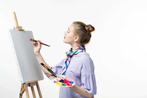 Pittore femminile vista frontale che si prepara a disegnare su una pittura a matita per disegnare un'immagine da cavalletto dell'artista della parete bianca