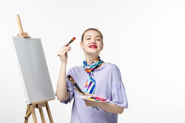 흰색 책상 이젤 그림 그리기 아티스트 연필 아트 페인트에 그릴 준비 전면보기 여성 화가