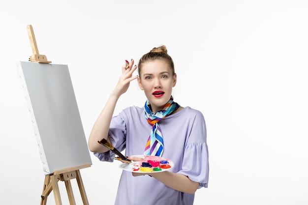 흰 벽 아티스트 이젤 그림 그리기 아트 페인트에 그릴 준비 전면보기 여성 화가