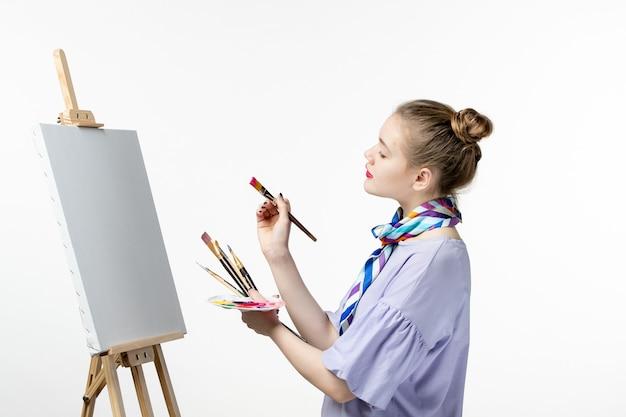 Вид спереди художница готовится рисовать на белой стене краска художественная картина фото художник мольберт карандаш