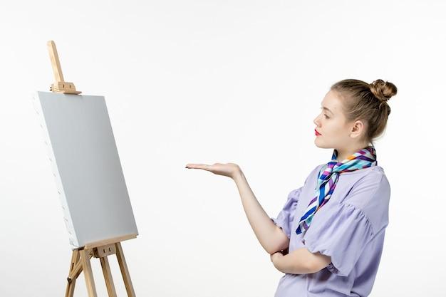 Вид спереди женщина-художник с мольбертом для рисования на белой стене рисунок искусство фото художник краска картина кисточкой