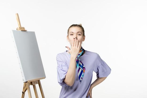 흰 벽에 그림을 그리는 이젤이있는 전면보기 여성 화가 사진 아티스트 전시회 페인트 드로잉 아트 감정