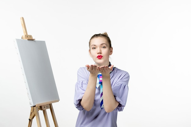 Front view female painter with easel for painting on white wall photo artist exhibition drawing art emotion