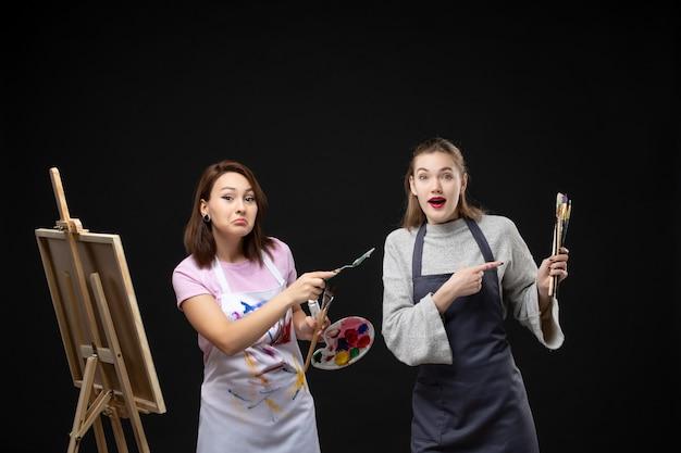 전면 보기 여성 화가 검은 배경에 그림을 그리기 위해 페인트와 술을 들고 그림 예술 컬러 아티스트 사진 그리기 그림