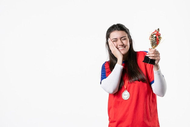 メダルと金のカップとスポーツ服の正面の女性
