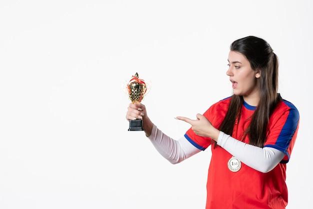 金のカップとメダルを持つ正面図の女性プレーヤー