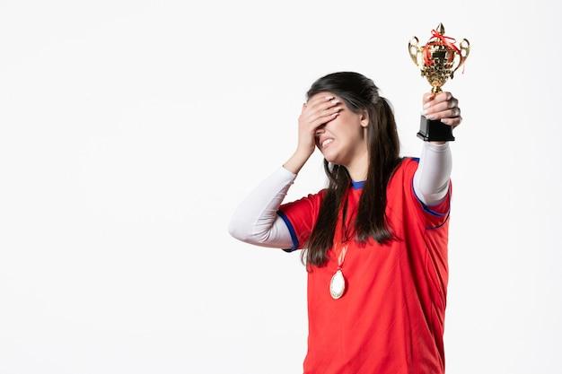 Вид спереди женский игрок с золотым кубком и медалью