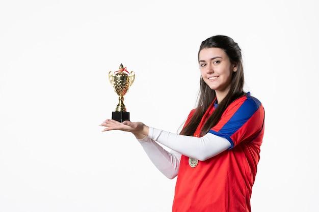 メダルとゴールデンカップの正面図の女性プレーヤー