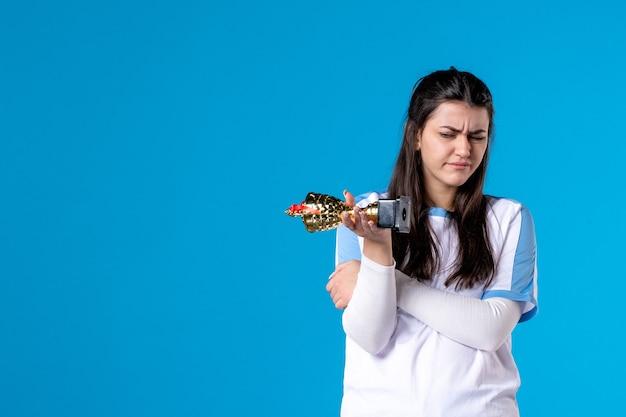 トロフィーを持つ正面図の女性プレーヤー