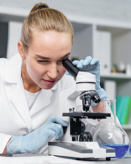 Front view of female researcher in the laboratory with microscope
