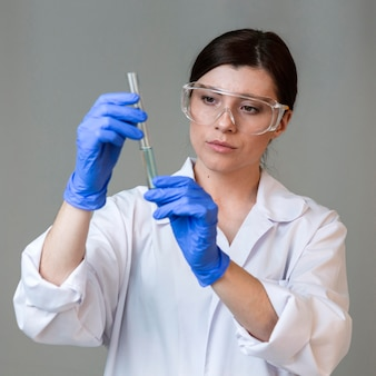 Front view of female researcher with safety glasses and test tube