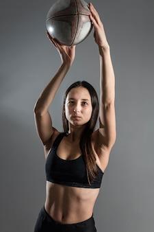 Vista frontale del giocatore di rugby femminile in posa con la palla