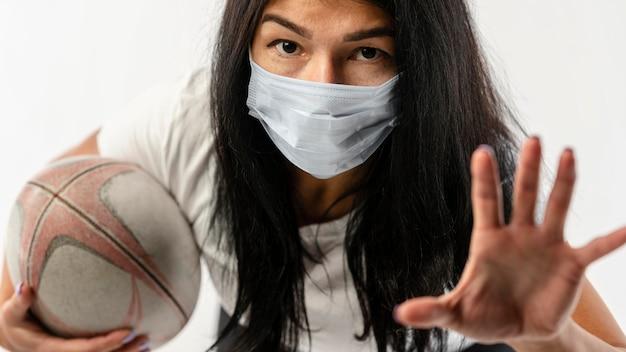 Vista frontale del giocatore di rugby femminile con maschera medica e palla