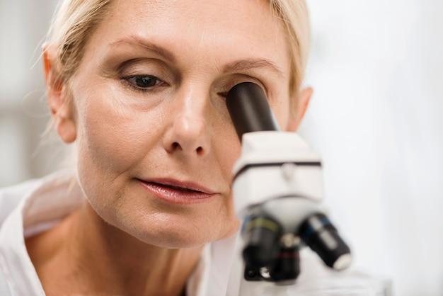 Vista frontale della scienziata in laboratorio che osserva tramite il microscopio