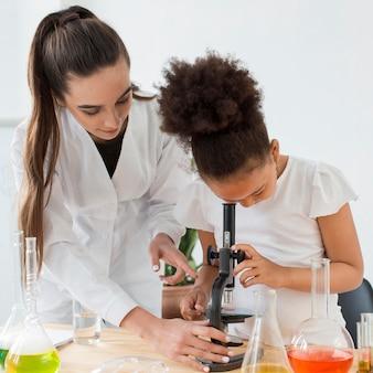 Vista frontale della ragazza d'istruzione della scienziata femminile da guardare tramite il microscopio