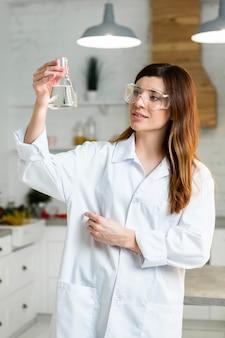 Vista frontale della scienziata con occhiali di sicurezza che tengono la provetta in laboratorio
