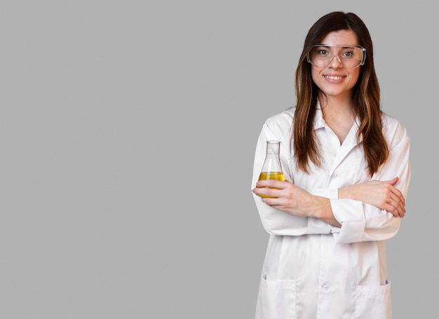 Front view of female scientist with safety glasses holding test tube with copy space