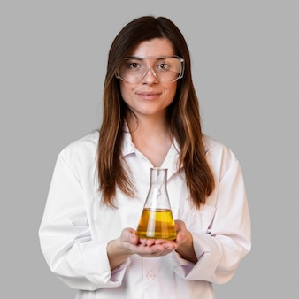 Front view of female scientist with safety glasses holding test tube