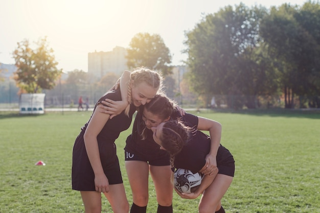Front view female soccer players embracing