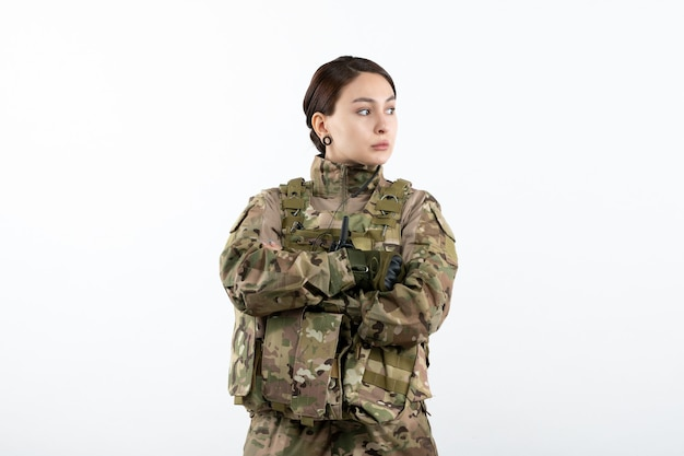 Front view of female soldier in camouflage on white wall