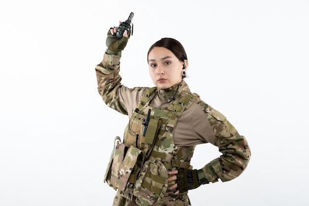 Vista frontale della soldatessa in mimetica con granata sul muro bianco