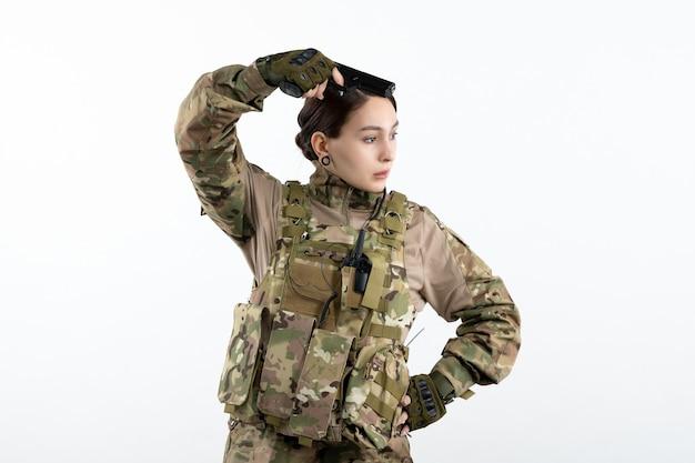 Soldato femminile di vista frontale in camuffamento con la pistola sulla parete bianca