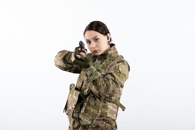 白い壁に銃を持った迷彩の正面女性兵士