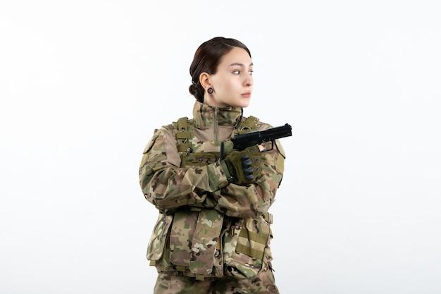 Вид спереди женщина-солдат в камуфляже с пистолетом на белой стене