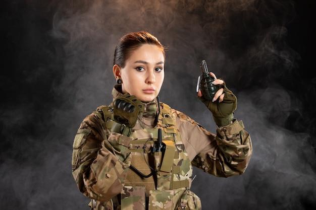 Vista frontale della soldatessa con granata in uniforme sul muro nero