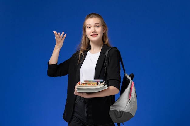 Front view female student in black jacket wearing backpack holding books on blue wall lesson school university college
