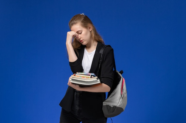 Front view female student in black jacket wearing backpack holding books on the blue wall school university college lessons
