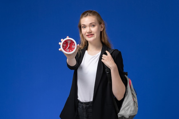 Studentessa di vista frontale in giacca nera che indossa uno zaino che tiene gli orologi sulle lezioni dell'università dell'università della parete blu