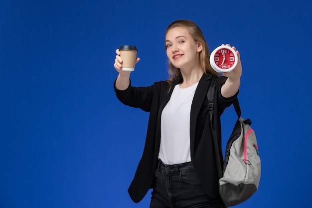Front view female student in black jacket wearing backpack holding clocks and coffee smiling on blue wall school college university lesson