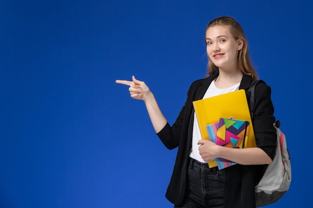 Front view female student in black jacket wearing backpack holding file with copybooks on blue wall college university lessons