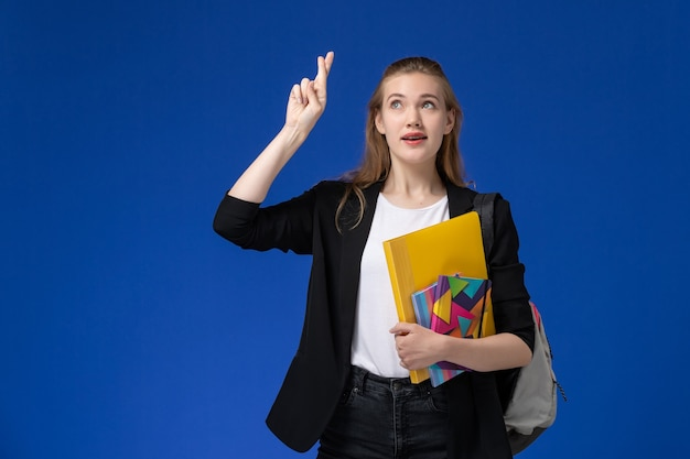 Front view female student in black jacket wearing backpack holding files with copybooks crossing her fingers on blue wall college university lesson