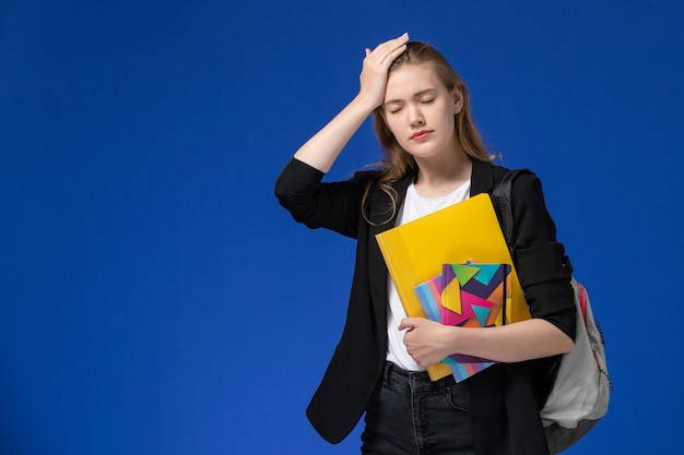 Front view female student in black jacket wearing backpack holding files with copybooks having headache on blue wall college university lesson