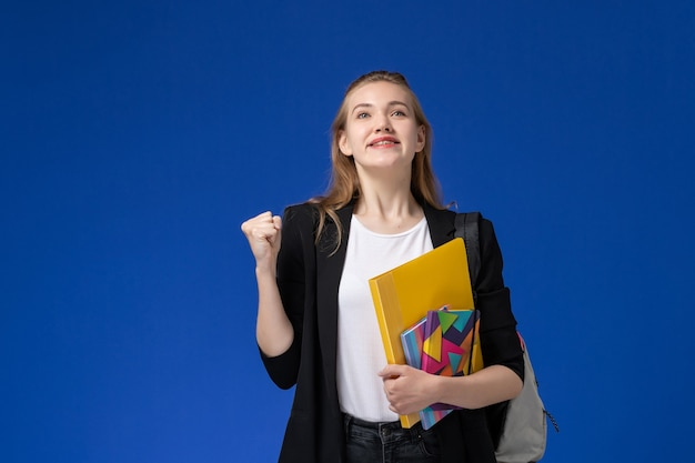 Front view female student in black jacket wearing backpack holding files with copybooks rejoicing on blue wall college university lesson