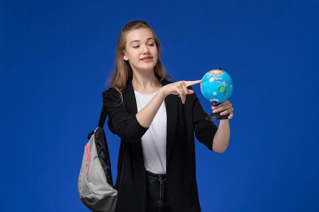 Studentessa di vista frontale in giacca nera che indossa zaino che tiene piccolo globo sulla terra blu di lezioni dell'università dell'università della scuola della parete