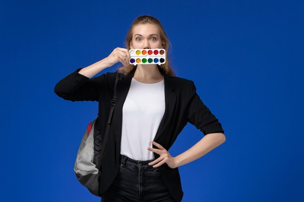 Studentessa di vista frontale in giacca nera che indossa lo zaino che tiene le vernici per disegnare sulla scrivania blu disegno scuola d'arte universitaria