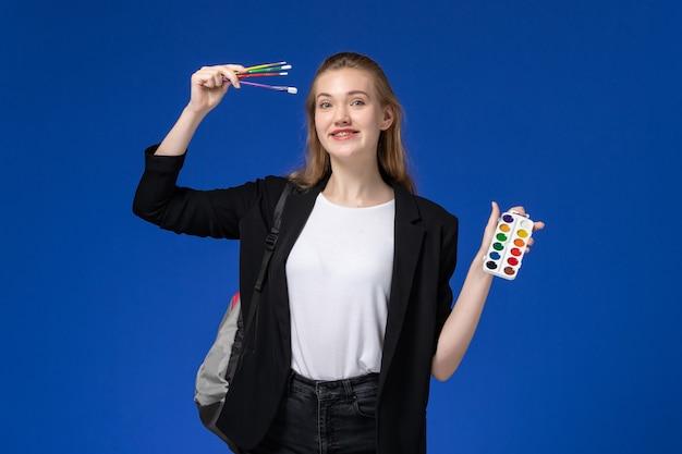 Studentessa di vista frontale in giacca nera che indossa uno zaino che tiene le vernici per il disegno e la nappa sul muro blu che disegna l'università della scuola d'arte